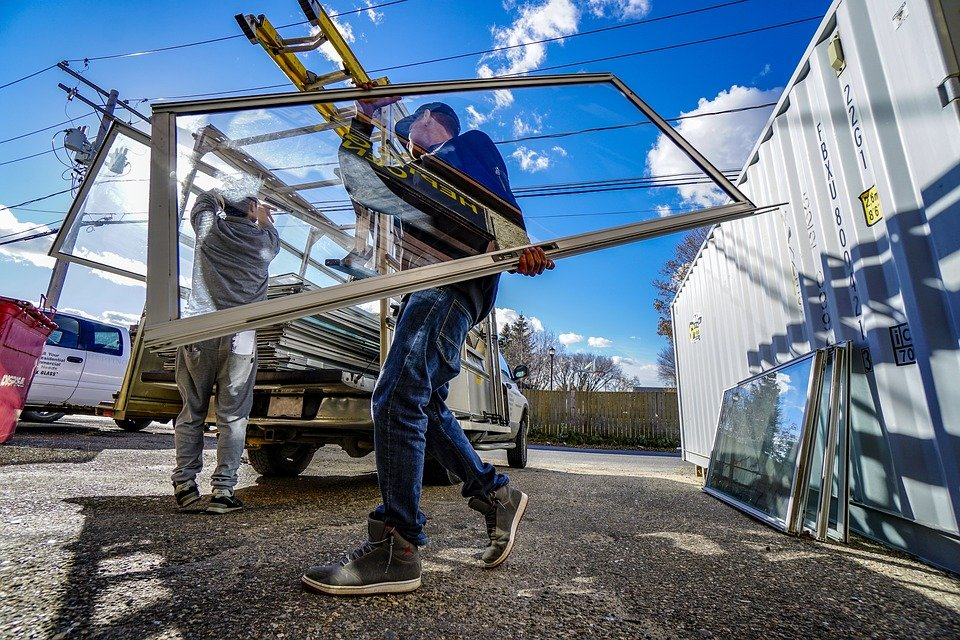 Workers carrying glass window
